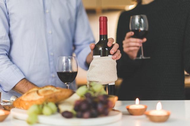 Muž drží v ruke fľašu vína a pohár s vínom.jpg