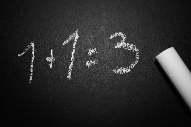 Čierna tabuľa s nápisom 1 plus 1 rovná sa 3
